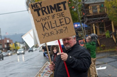 """David Sale holds a sign at a demonstration reading """"Hey Trimet What if she killed your kid?"""""""