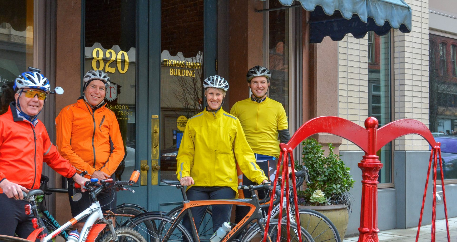 Four people in brighlty colored jackets stand with bicycles in fornt of law office.