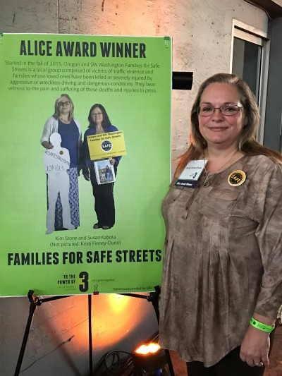 Kristi Finney Dunn stands next to a posterboard proclaiming her the winner of the Alice Award for transportation advocacy.