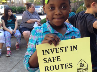 Young girl w braids holding sign